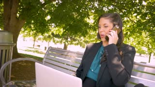 Beautiful powerful female business executive happily working with laptop and talking on her smart phone outside handheld stabilized slow motion shot