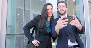 Beautiful well dressed millennial man and pretty woman in her 30s take selfie with smart phone technology for social media outside business complex in 4k