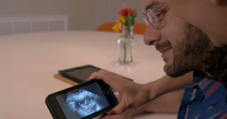 Beautiful young expecting parents couple looking at ultrasound of baby on smart phone