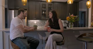 Beautiful young happy smiling couple in love drinking coffee and talking in their kitchen in the morning - wide dolly shot