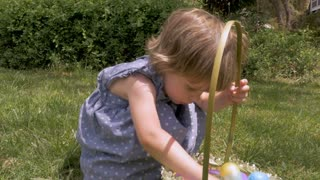 Beautiful young innocent 2 - 3 year old girl looking at her Easter basket in slow motion