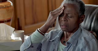 Black baby boomer senior in her 60s rubbing her temples to relieve headache pain from stress, illness, or allergies.