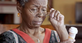 Black senior woman putting on glasses to read medication instructions of her prescription bottle for her health care