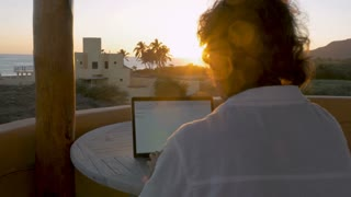 Blogger, writer, or graphic designer man working on laptop at home office at beach at sunrise or sunset with lens flare