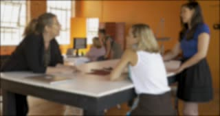 Blurred background plate of a busy open office with businesswomen working
