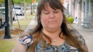 Bored uninterested tired heavy woman yawning outside on city sidewalk waiting