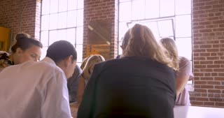Camera circles around a diverse group of business men and women looking at blue prints on a table together