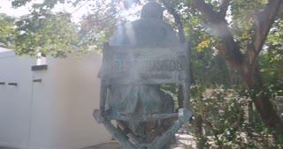 Camera circles around the John Huston statue in Isla Cuale park in Puerto Vallarta, Mexico