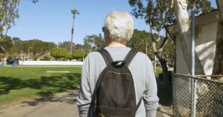 Camera following a happy healthy senior man with gray hair walking through a park with a small backpack on a beautiful sunny day - stabilized shot