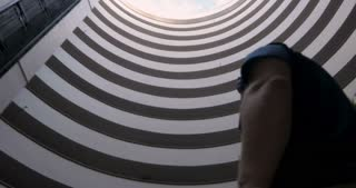 Camera moving around a man looking up at the sky through the center of a futuristic round building
