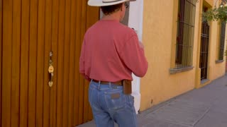 Caucasian man in a cowboy hat walking and playing with a Mexican toy called a balero