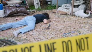 Caucasian white male dead murdered body lying on ground at crime scene with Police Line Do Not Cross tape outside with hammer