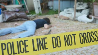 Caucasian white man dead murdered body lying on ground at crime scene with Police Line Do Not Cross tape outside with hammer rack focus