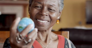 Cheerful African American woman looking at world map globe in her hand and smiling - rack focus