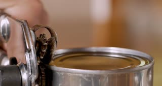 Close up of a hand using a manual can opener to open a can of food and removing the top of the lid