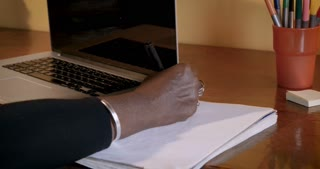 Close up of a mature African American woman writing in a notebook next to her laptop at her desk