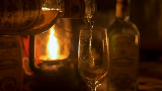 Close up of a person pouring tequila in a champagne flute lit by lantern in a dark tasting room