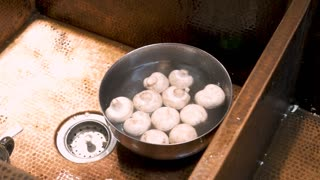 Close up of a person rinsing white mushrooms in a stainless steel bowl with fresh water
