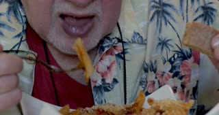 Close up of a senior man in his 70s or 80s eating a bowl of penne pasta with red tomato sauce and cheese wearing a Hawaiian shirt in a restaurant or cafe