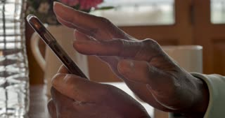 Close up of a woman's black hands swiping, scrolling and using a smart phone going through messages, notifications and browsing a mobile application