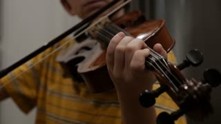 Close up of a young boy's fingers playing a violin in slow motion