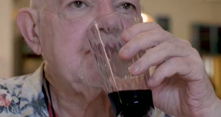 Close up of an elderly senior man drinking red wine and chewing food in a restaurant or cafe
