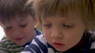 Close up of two cute young children a boy and girl focused on playing together in slow motion