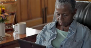 Concerned elderly senior black woman in her 50s or 60s reading a digital tablet in her living room during the day