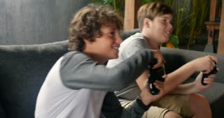 Couple of young pre teenage boys playing video games on a sofa together on a rainy day smiling and having fun