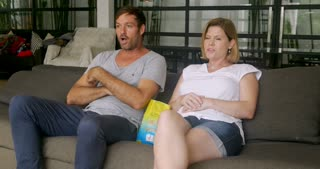 Couple watching television together starts celebrating and then is interrupted when the tv goes out in their home
