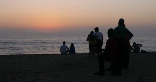 Couples, musicians, and tourists watching and enjoying a picturesque sunset at the ocean as waves come along the beach