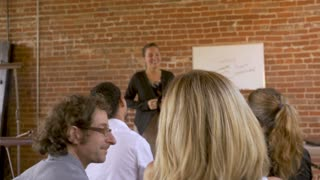 Coworkers smiling and attending a employee meeting on teamwork with a presenter using a whiteboard in slow motion