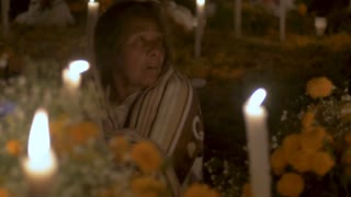 CUCUCHUCHO, MEXICO - NOVEMBER 1, 2016 - Old indigenous woman celebrating Day of the Dead at a graveyard alter at night wrapped in a blanket near Patzcuaro, Michoacan