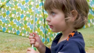 Cute adorable little 2 - 3 year old girl holding umbrella turns and walks away in slow motion