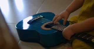 Cute baby playing with a small toy guitar while sitting on a floor