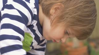 Cute little girl concentrating and playing in a garden outside in slow motion