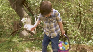 Cute young boy 4 - 5 years old holding an Easter basket walks towards his mother holding a white basket in slow motion