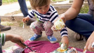Cute young boy and girl coloring easter eggs and making a mess with their mom in slow motion outside
