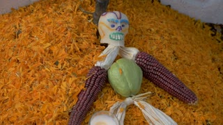 Day of the Dead sugar skull doll made with corn cobs on Marigold flowers on a grave in a cemetery outside of Patzcuaro, Michoacan