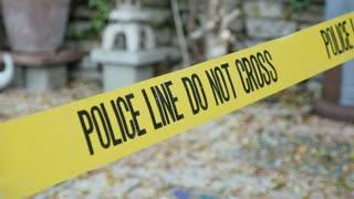 Daytime crime scene tape outside home Police Line Do Not Cross dolly shot