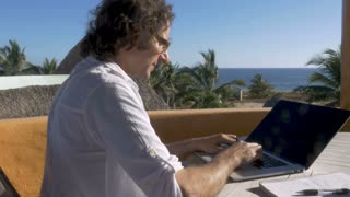 Digital nomad man working on laptop stops to answer smart phone with ocean view