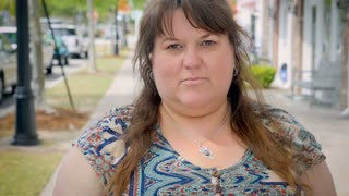 Disappointed frustrated full figured plus size woman gives the thumbs down shaking her head no outside on urban city sidewalk
