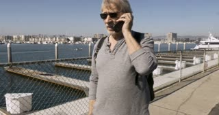 Distinguished healthy handsome senior man in his 60s or 70s talking on a flip phone and walking in a marina along the ocean with luxury condominiums and sailboats in the background - stabilized shot