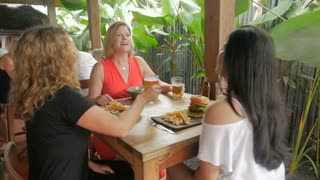 Diverse ethnic group of beautiful women laughing, drinking, eating, and celebrating in a restaurant in slow motion - stabilized shot