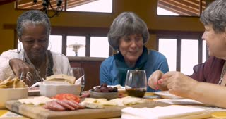 Diverse group of elderly women in their 60s eating healthy snacks, gossiping, talking and laughing together - dolly shot