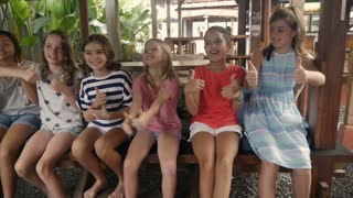 Diverse group of happy young girls giving the thumbs up and chair dancing celebrating