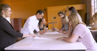 Diverse group of men and women looking at blue prints for their expanding business while sitting around a large table