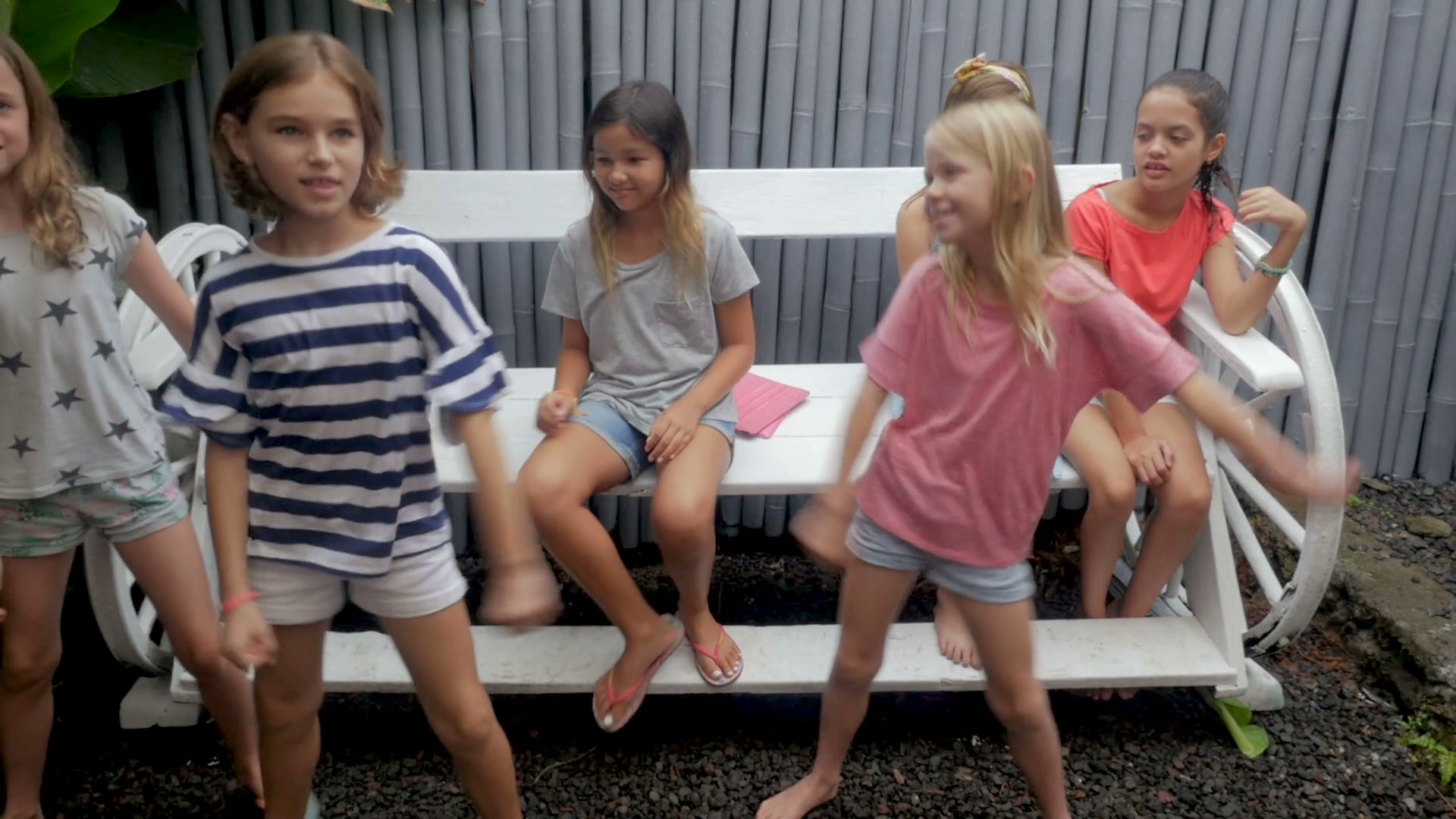 Diverse group of young mixed ethnic girls ages 7 - 12 getting off a bench to join their friend dancing in slow motion Stock Video Footage - Storyblocks