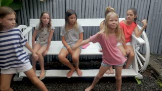 Diverse group of young mixed ethnic girls ages 7 - 12 getting off a bench to join their friend dancing in slow motion
