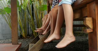 Diverse mixed racial group of young girls with bare feet and shorts swinging their legs while sitting outside